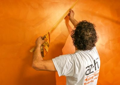 az-h Malermeister vor einer Wand in der Unternehmensfarbe